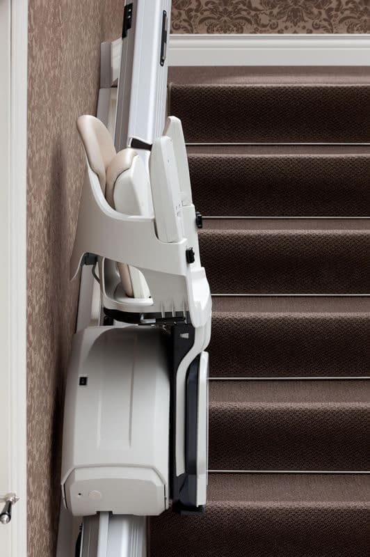 HomeGlide ThyssenKrupp Straight Stairlift from 1st Choice Stairlifts folded up and parked on intermediate parking station powered hinge rail