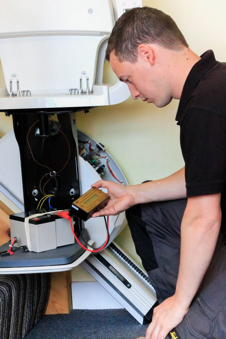 engineer servicing a stair lift battery pack